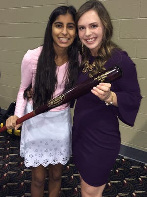 Leena Vyas (left) and Sydney Conn hold a baseball bat, awarded to the Big Idea Pitch winners by the Innovation Connector. They also won a $5,000 prize.