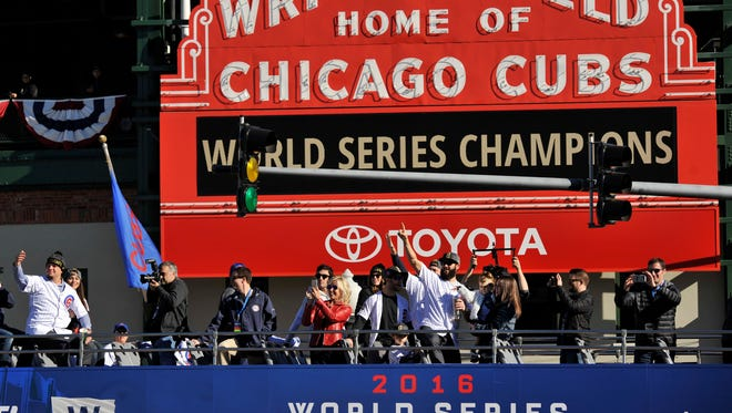 Chicago Cubs baseball player Jake Arrieta, center right with a finger in the air, and Kyle Schwarber, far left, wave to fans during a parade Nov. 4, 2016, outside Wrigley Field honoring the World Series champions in Chicago.