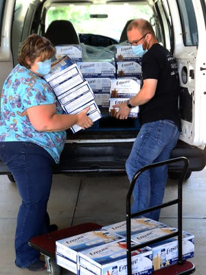 Morgan Osman, River Valley Regional Food Bank agency relations director, left, and Justin Bates, RVRFB Marketing director, deliver 30 cases of Ensure, Monday, June 15, 2020, to the Donald W. Reynolds Cancer Support House helping the United Way member provide  cost-free, non-medical support programs and services to cancer patients and caregivers, and to provide educational programs to the community.