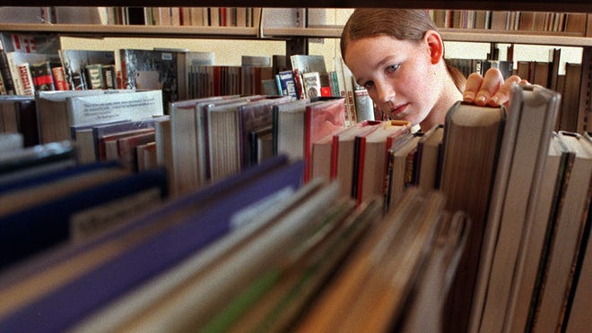 Allie Dillavon, 12, of Altoona examines books in the young adult section during the grand opening of the Altoona Public Library in 1998. Like many libraries in Iowa, the Altoona Public Library has been confused with another out-of-state library bearing a similar name. A police detective working a case in Altoona, Pennsylvania, called the library in suburban Des Moines with a request for information.