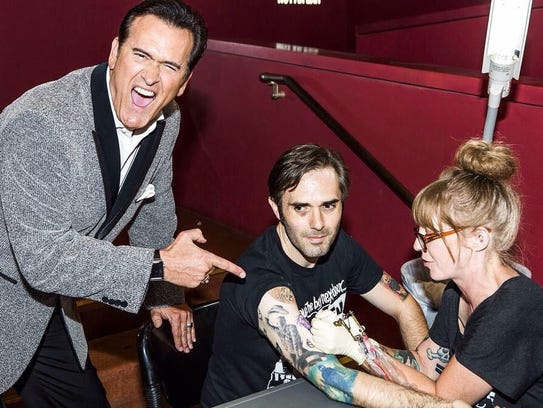 """Bruce Campbell watches as a fan gets a free """"Evil Dead"""""""