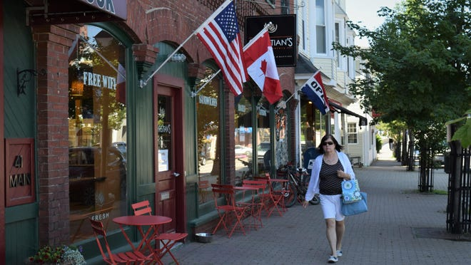 A shopper walks by local businesses in downtown Kennebunk on Wednesday morning.