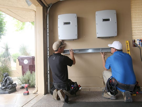 Patrick Kelley, left, and Leif Soderlind of Renova Solar install two solar inverters in Darlene Montgomery's garage at the Bermuda Dunes Country Club on May 14, 2015.