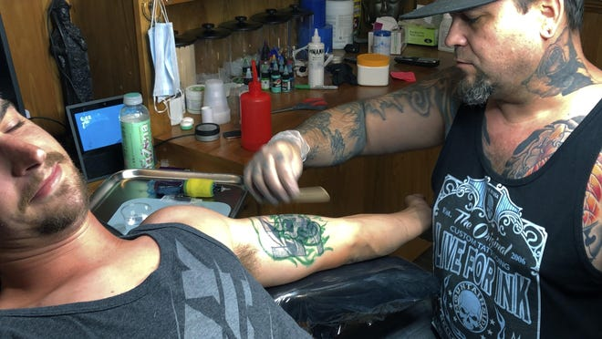 In this Friday, June 19, 2020, photo, tattoo artist Alexander Lawrence, right, prepares to cover up a tattoo that contained the image of a swastika on the arm of Dylan Graves Bellows Falls, Vt.  Lawrence said he has always covered up or removed offensive tattoos for free, but the demand has increased since the death of George Floyd and the resurgence of the Black Lives Matter movement.