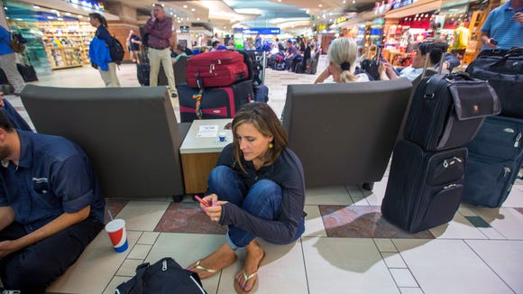 Julie Saso, of San Jose, waits with hundreds of other travelers at Phoenix Sky Harbor International Airport's terminal 4 as police search for an armed suspect, Thursday afternoon, Sept. 18, 2014. Saso just arrived to surprise her niece on her 8th birthday.