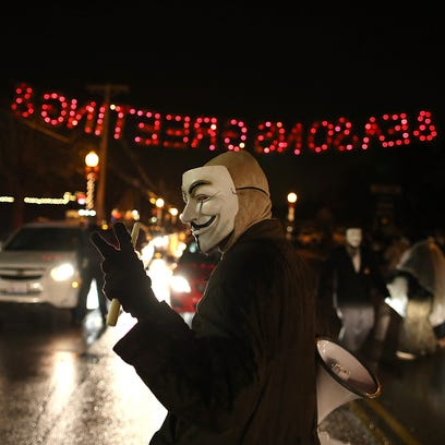 A demonstrator wears a Guy Fawkes mask as he protests