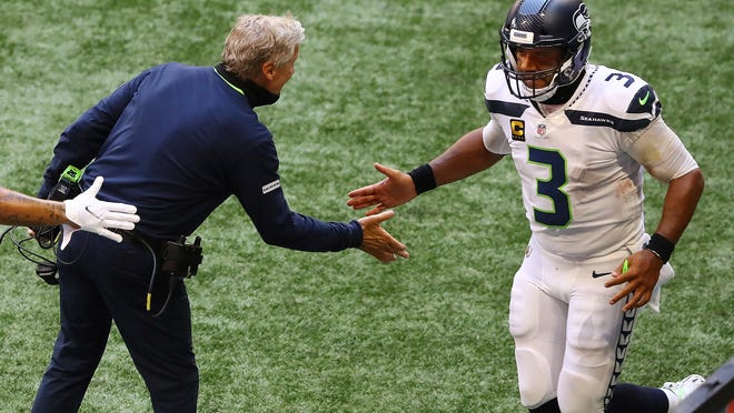 Seahawks quarterback Russell Wilson celebrates with coach Pete Carroll after throwing a touchdown pass to D.K. Metcalf against the Falcons.