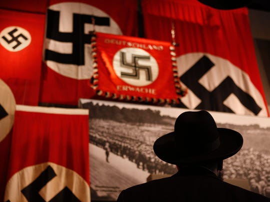 A man looks at exhibit showing the Nazi flag during