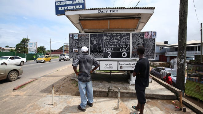 Liberians read a story about Ebola on a public chalkboard in Monrovia on July 10, 2015. Liberia has had six new cases of Ebola after the World Health Organization declared the country free of Ebola on May 9, 2015.