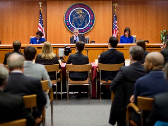 """Federal Communication Commission (FCC) Chairman Tom Wheeler, center, with FCC Commissioners from l-r, Ajit Pai, Mignon Clyburn, Jessica Rosenworcel, and Michael O'Rielly during a hearing and vote on Net Neutrality in Washington, Thursday, Feb. 26, 2015. The FCC has agreed to impose strict new regulations on Internet service providers like Comcast, Verizon and AT&T. The regulatory agency voted 3-2 Thursday in favor of rules aimed at enforcing what's called """"net neutrality."""" That's the idea that service providers shouldn't intentionally block or slow web traffic, creating paid fast lanes on the Internet."""