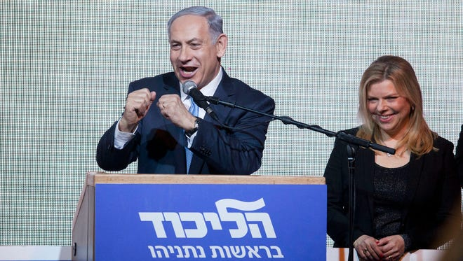 Israeli Prime Minister Benjamin Netanyahu greets supporters at the party's election headquarters In Tel Aviv on Wednesday, March 18, 2015.