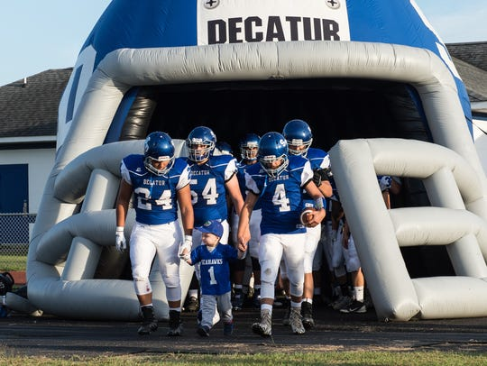 Stephen Decatur football players walk with Bob Knox's