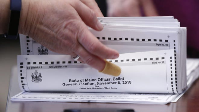 In this Nov. 12, 2018 file photo, ballots are prepared to be tabulated in Maine's 2nd Congressional District election in Augusta, Maine.