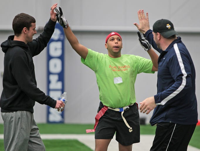 Jerry Moore, center, is congratulated by former Indiana Colts players John Standeford, left, and Rick DeMulling, right, after a touchdown in a flag football game, during a Mini Combine and Football Clinic for Special Olympic athletes at the Colts Complex, Saturday, February 22, 2014, held as a complement to the annual NFL Scouting Combine held at Lucas Oil Stadium.  The event was sponsored by the Knights of Columbus, Indiana Special Olympics, and Catholic Athletes for Christ.  Four former Colts players also volunteered to help train and inspire the athletes.