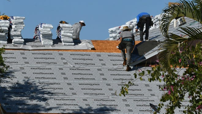 Roofing crews work on a project in Viera. Wind-resistant reroofing projects are among the improvements that would qualify under the Property Assessed Clean Energy program.