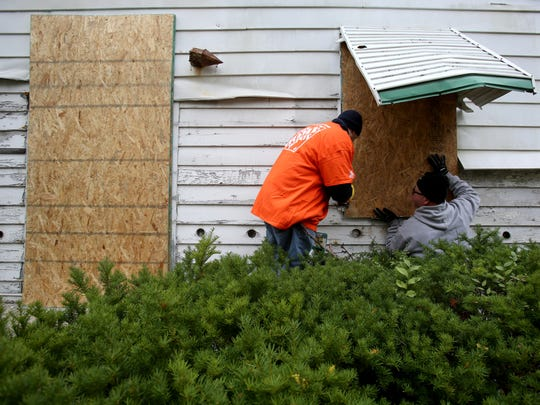 Thomas Jabtecki, 35, of Harper Woods, left, and John Park, 37, of Macomb Township, both part of Home Depot's volunteer program, board up one of the windows of a abandoned home on Joann Street in Detroit.