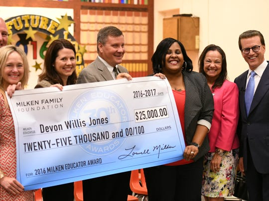 Jeanerette Elementary Principal Devon Willis-Jones gets help holding her oversized Milken Educator Award check from visiting dignitaries. From left, Louisiana Department of Education Network Leader Francis Touchet; Louisiana Department of Education Talent Project Director Joni Marionneaux Lacy; Louisiana Board of Elementary and Secondary Education (BESE) Vice President Dr. Holly Boffy; Iberia Parish School District Superintendent Dale Henderson; Recipient Devon Willis-Jones; Louisiana BESE Member Sandy Holloway; and Lowell Milken, chairman and co-founder of the Milken Family Foundation.
