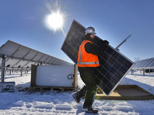 Tim Bode of Hunt Electric, St. Paul, carries a solar panel as he and others work to install an array of 616 new panels in November 2014 at the St. John's Abbey Solar Farm.