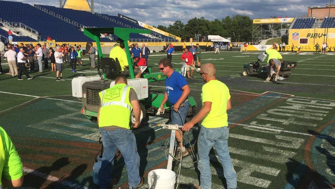 Workers try to repair the midfield area of Tom Benson Hall of Fame Stadium before the Hall of Fame Game on Sunday in Canton, Ohio
