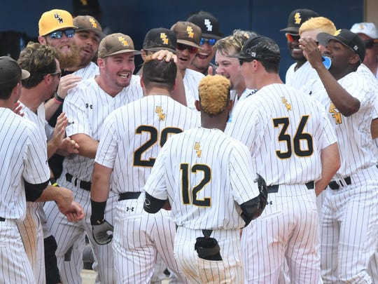 Southern Miss players celebrate with Bryant Bowen after his home run in the Conference USA tournament championship game against FAU.