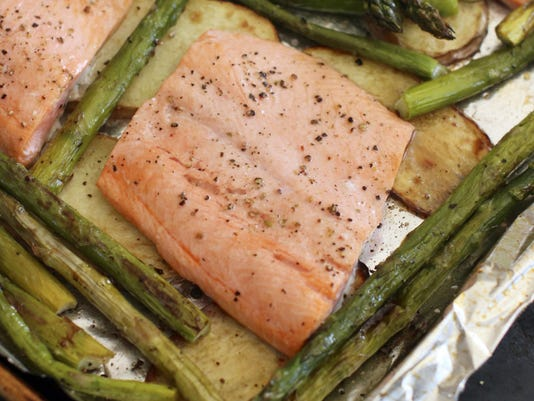 Baked steelhead trout with asparagus, potatoes and herbs.