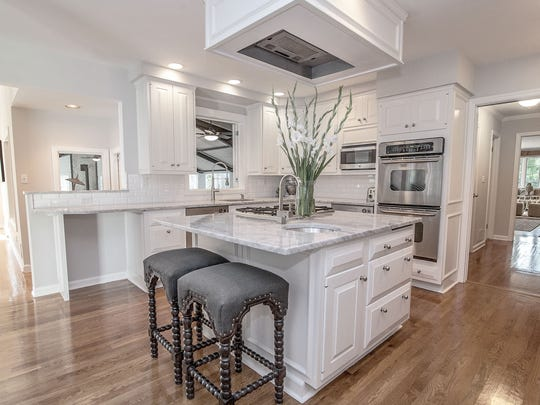 The center island in the kitchen has a Carrera marble counter with breakfast bar.