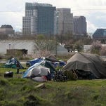 A homeless tent city sits in front of the Sacramento skyline.
