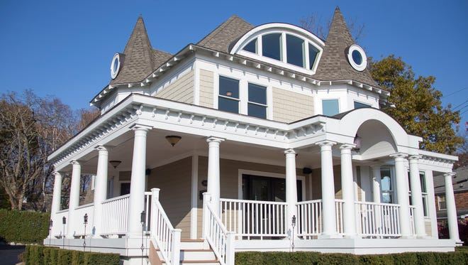This 1896 Victorian house got a 21 Century postmodern makeover with details like the crescent moon-shaped slash in the roof in the roof, and the exaggerated portico added to the porch.