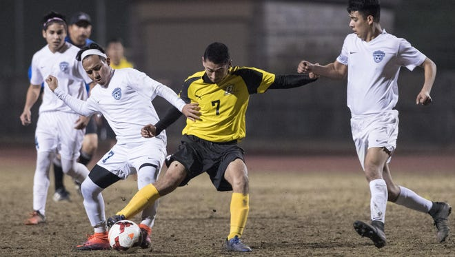 Redwood's Josue Chavarria, left, and Golden West's Enrique Ibarra battle for possession in a West Yosemite League high school boys soccer game Tuesday, January 31, 2017.