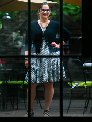 Patricia Miller wears a black and white dotted A-line dress by Just...Taylor from Marshall's with a knit black cardigan and black suede and patent leather shoes with heel by Adrienne Vittadini.