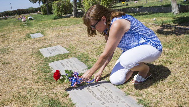 Sharon Johnston places flowers at the grave of Spc. Gerald Lubbehusen at Holy Cross Cemetery in Avondale. She is part of a national effort to track down the pictures of every military service person killed in the Vietnam War for an education center near the VIetnam Veterans Memorial in Washington, D.C.