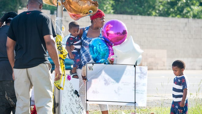 Akeiya Mitchell, center, and her family  pay their respects at the makeshift memorial for the hit-and-run victims at the corner of Cervantes and M Streets in Pensacola on Thursday, June 7, 2018.  Mitchell's niece Nephateria Monique Williams, 28, and 8-month-old Neariaah Ikerria Williams were killed by the driver.  Neariaah's mother Quineka Tyon Baldwin, 27, was also injured during the incident.