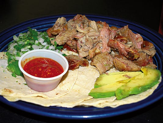 The carnitas plate (8.50) has pork, lettuce, red onions, avocado and spicy green salsa, served on white corn tortillas.