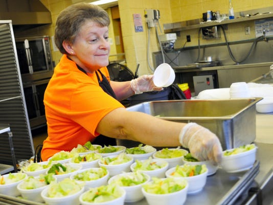 A cafeteria worker prepares salads for students recently at Fairview Elementary School.
