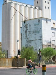 A bicyclist bikes down Mill Avenue past the Hayden Flour Mill in Tempe.