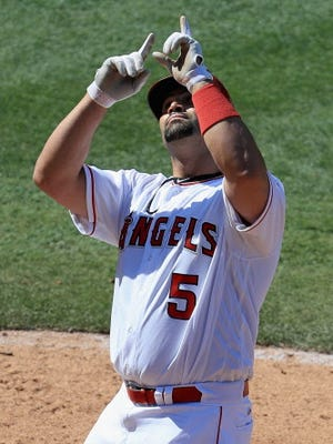 Albert Pujols points to the sky after hitting a home run in the ninth  inning against the Seattle Mariners.