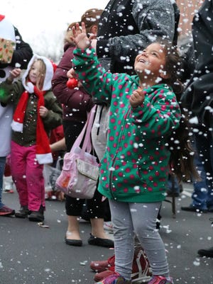 Alexianna Shetzer, 5, of Fremont, enjoys the snow from one of the floats during the downtown Christmas parade on Saturday.