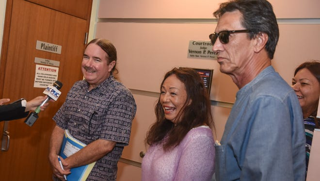 Singer Yvonne Elliman-Alexander, center, and husband Allen Alexander, right, stand with their attorney Mike Phillips, as he addresses questions form the media after an ex parte hearing was held for his clients at the Superior Court of Guam on Wednesday, Aug. 30, 2017. The singer and her husband appeared before Judge Vernon Perez to request permission to return to their home in Hawaii until future proceedings regarding their drug case pending in the local court.