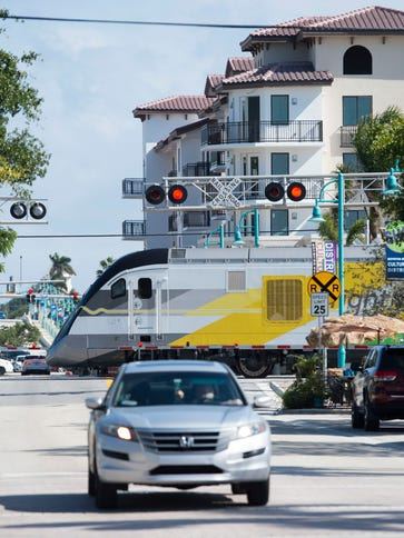 A Brightline train traveling north crosses East Ocean