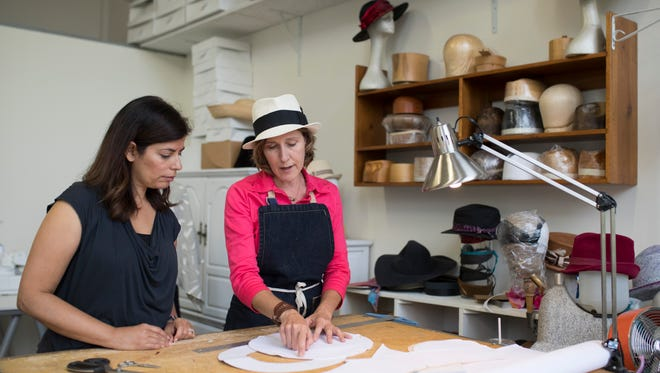 Louisville Bespoke founder Yamilca Rodriguez, left, and milliner Sarah Havens discuss a designinside the Louisville Bespoke collaborative space at the Hope Worsted Mills building in the Germantown neighborhood. Aug. 29, 2017