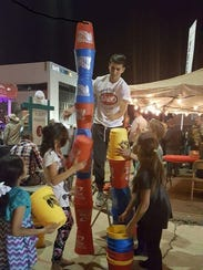 Kids play with giant stack cups provided by the city's