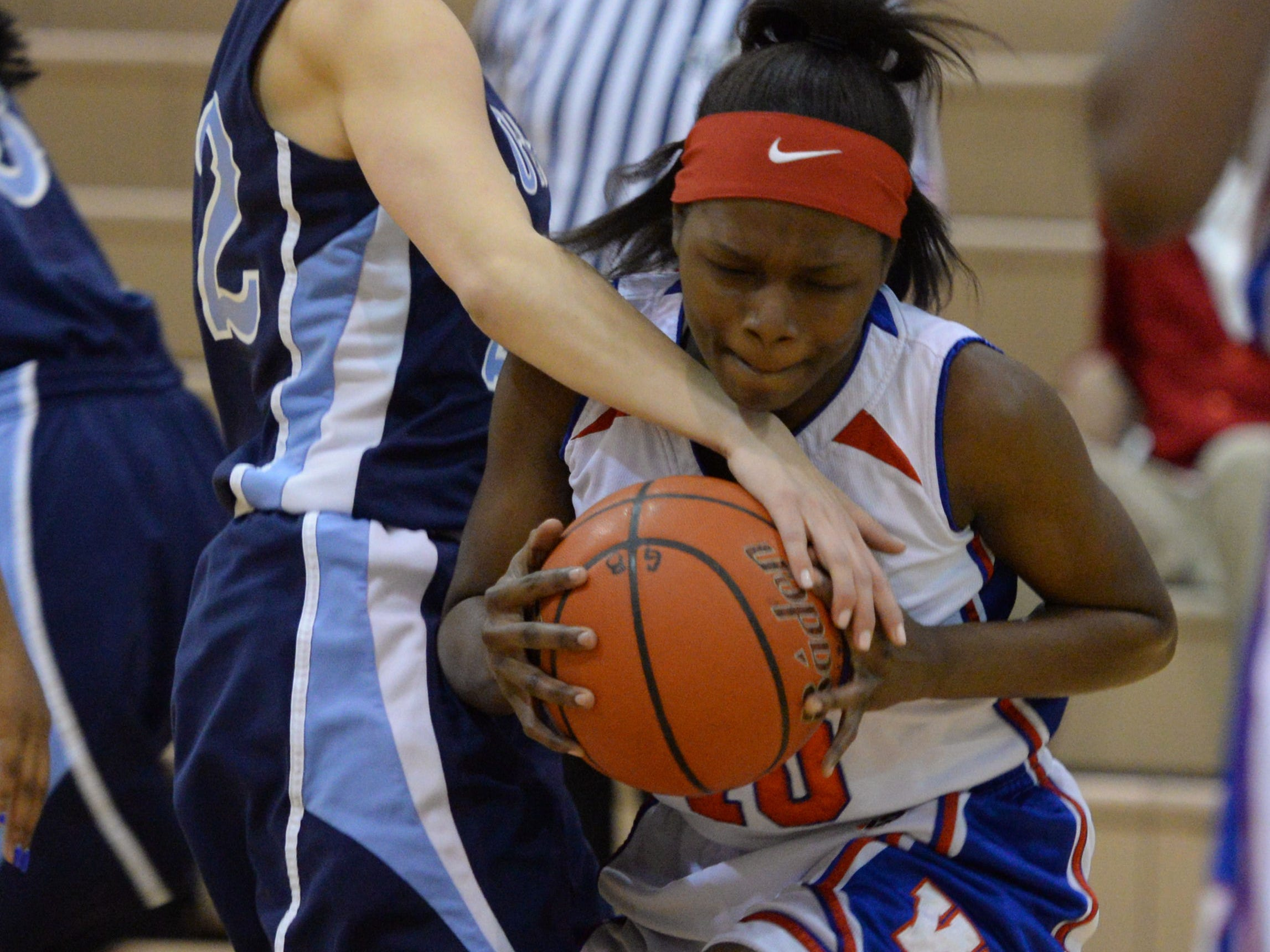 Woodlawn's Aliyah Carter pulls in a rebound past Loyola's Sydney Mouser.