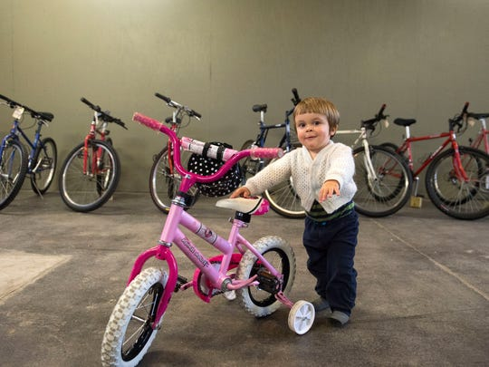 18-month-old Joseph Hulse plays with a bike at DreamBikes