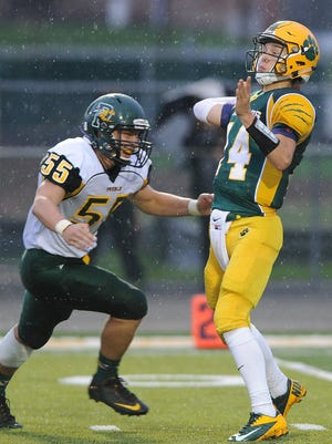 Ashwaubenon quarterback Will Ark (14) throws under heavy pressure by Green Bay Preble lineman Zach Kratky (55) at Goelz Field on Friday. See more pictures from the game at greenbaypressgazette.com.