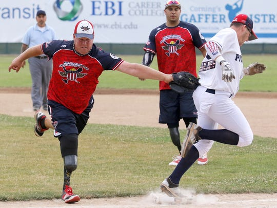 Wounded Warrior Amputee Softball Team first baseman Chris Hutton reaches out to tag Ethan Daily, of the Elmira Pioneers, during an exhibition game July 16 at Dunn Field.