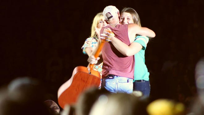 Jenna Terek, right, gets a hug from Kenny Chesney as singer Grace Potter looks on from the stage at Lambeau Field on Saturday night. The 20-year-old fan from Wausau was given Chesney's autographed guitar.