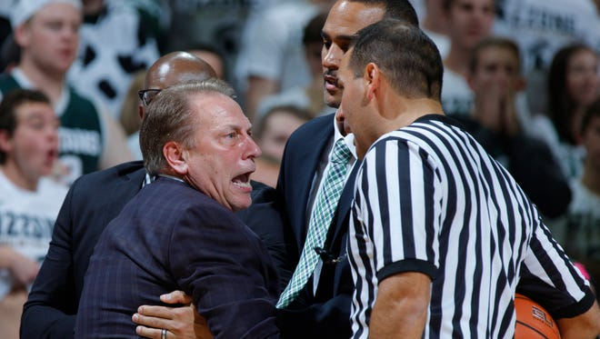 Michigan State coach Tom Izzo is held back by assistant coach Mike Garland, left rear, and director of basketball operations David Thomas, center, as he argues a call with official Bo Boroski, right, during the first half of MSU's 78-77 win Sunday at Breslin Center.