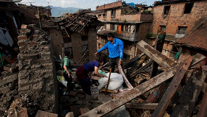 A Nepalese family collects belongings from their home destroyed in Saturday's earthquake, in Bhaktapur on the outskirts of Kathmandu, Nepal, Monday, April 27, 2015. A strong magnitude earthquake shook Nepal's capital and the densely populated Kathmandu valley on Saturday devastating the region and leaving tens of thousands shell-shocked and sleeping in streets.