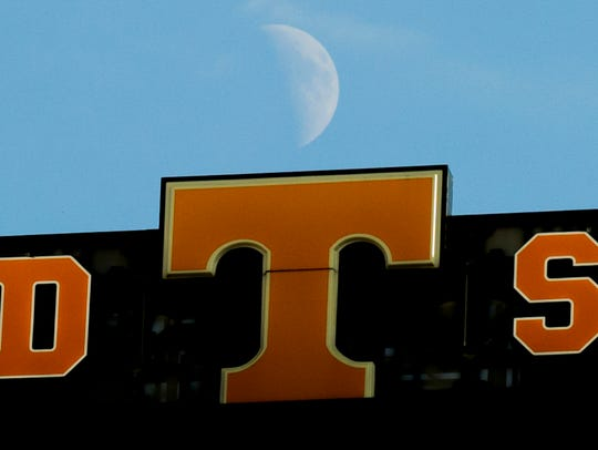 The moon rises behind the scoreboard during a game