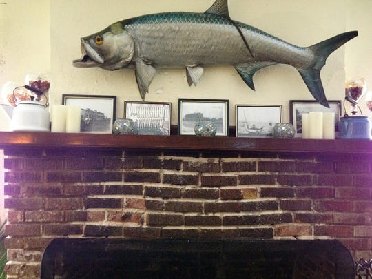 LAURA RUANE/THE NEWS-PRESS Mounted fish and photos of long-ago catches accent fireplace mantel at Tarpon Lodge at Pine Island's Pineland community
